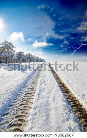 snowy winter road on one side of a field and woods on the other against the backdrop of a stormy sky. natural composition