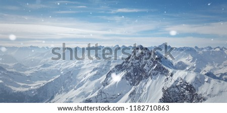 Snowy winter scenery with high moutains and snowflakes.