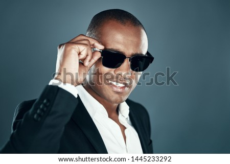 So charming! Charming young African man in full suit looking at camera and adjusting eyewear while standing against grey background
