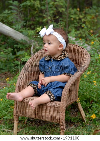 So Cute- A little girl dressed in denim sitting in a child's wicker chair looking so cute