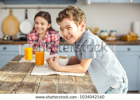 So joyful. Handsome delighted little dark-haired boy laughing and having healthy breakfast with his sister and the girl smiling in the background