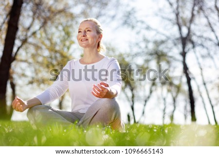 So peaceful. Cheerful peaceful woman sitting in the grass while meditating #1096665143
