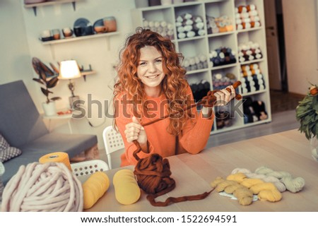 So pleased. Charming longhaired girl looking straight at camera and holding brown yarn in both hands