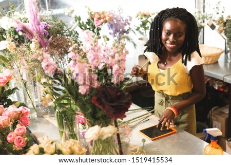 So pleased. Cute international florist keeping smile on her face while looking at plants