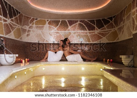 So relaxing. Happy nice couple sitting in sauna while enjoying their relaxation together #1182346108