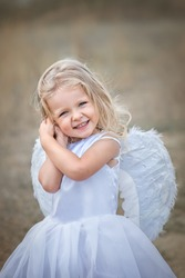 So sweet  beautiful blonde angel with blue eyes in a white ball gown with white feather wings smiling clasped hands under her cheek. Vertical photo.