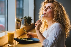 So tasty delicious yummy meal! Close up photo portrait of blond curly lady with closed eyes tasting healthy food from dish at cafe or restaurant in evening time.