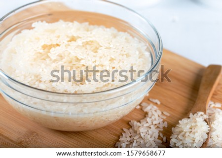 Soaked rice, grain, cloudy liquid water in glass bowl on wooden background Stock photo ©