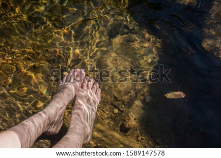 Soaking one's feet in the water of the stream Stock fotó ©