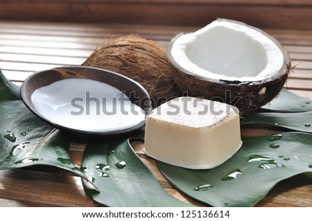 soap and coconut milk with coconut arranged on a wooden pallet