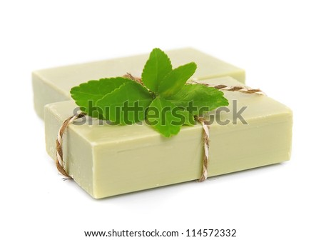 Soap and leaves of green tea on a white background