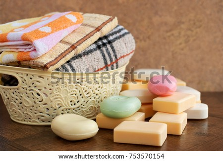 Soap and towels in the basket. Bath towels in the laundry basket. Solid soap is scattered on the table. Soap is different in color and shape. Soap and towels for hygiene and cleanliness.