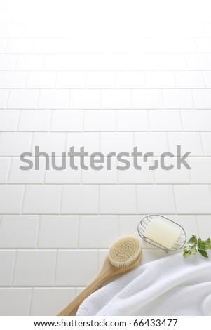 Soap,brush,and towel on white tile floor
