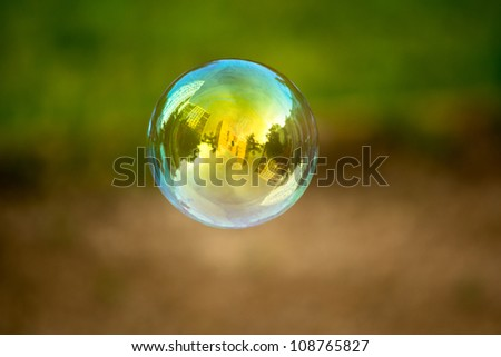 Soap bubble flying. Houses reflected in.