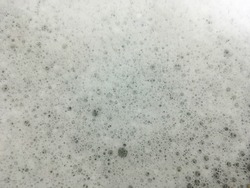 Soap bubbles are on the dirty water background after washing the dishes.