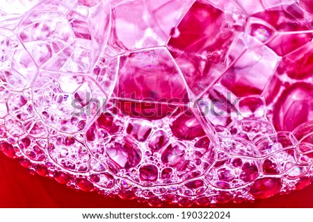 Soap bubbles in red liquid texture.