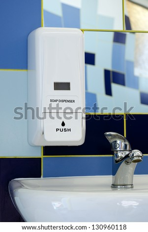 Soap dispenser above the sink or basin in blue tile bathroom.