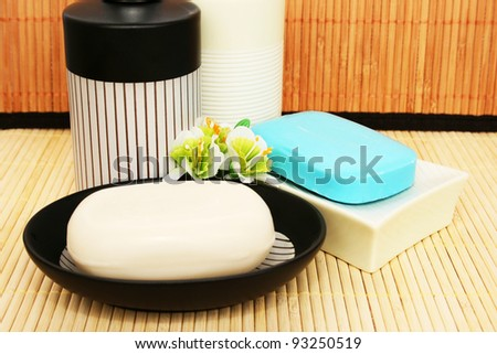 Soap dispensers and bars on bamboo background.