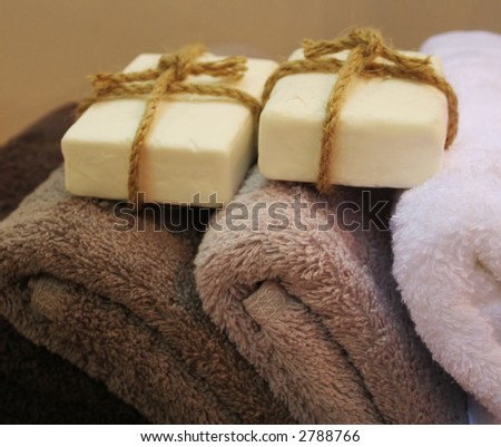 Soap wrapped with rope on top of a pile of towels - home and decor