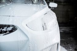 Soapsuds drip down the front of a white sedan. Covered in car shampoo to clean off dirt and grime. At a carwash or auto detailing service.