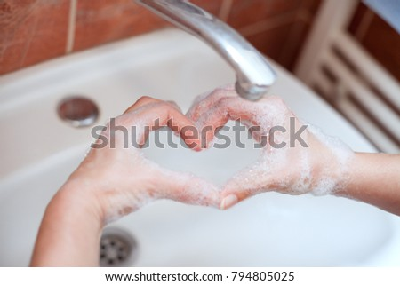 Soapy hand making heart shape in bathroom. Hand hygiene. Love your hands.
