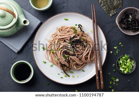 Soba noodles with sauce and garnishes. Japanese food. Top view. Black slate background. Stock fotó ©