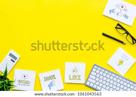 Socail media icons on work desk of marketing expert. Digital promotion of goods and services. Yellow background top view copy space
