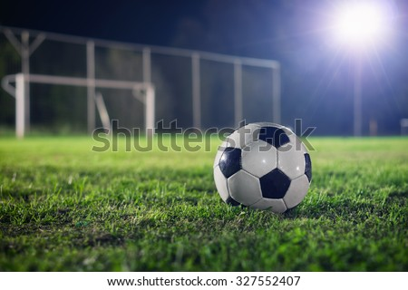 Soccer at night. Classical football on the playground, reflector made a beautiful lens flare in the background