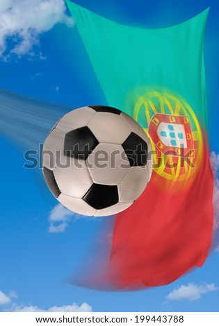 Soccer ball flying fast with Portugal flag in background.