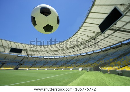 Soccer ball flying over bright green grass football pitch
