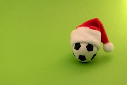 Soccer ball in a red Santa Claus hat. The concept of sports New Year's gift. Green background. Copy space.