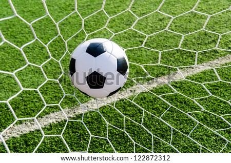 Soccer ball in Goal net with green grass field.