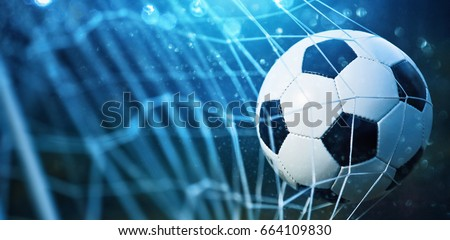 Soccer ball in goal on blue background #664109830