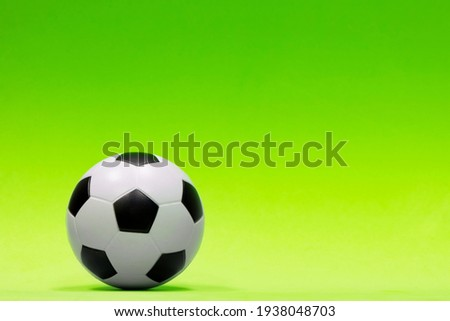 Soccer ball isolated against a plain green background with gradual color shading. Conceptual header image with copy space on the right side.