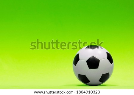 Soccer ball isolated against a plain green background with gradual color shading. Conceptual image with copy space on the left side.