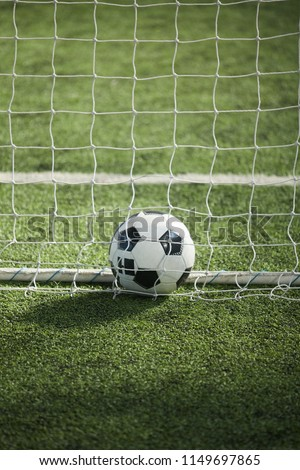 Soccer ball lying on green grass on empty football field behind net