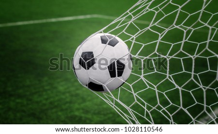 Soccer ball on goal with net and green background, this photo can use for football, sport, goal, score, shoot and target of business concept