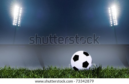 Soccer ball on grass field with spotlights - stock photo