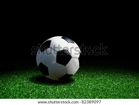 Soccer ball on grass over black background