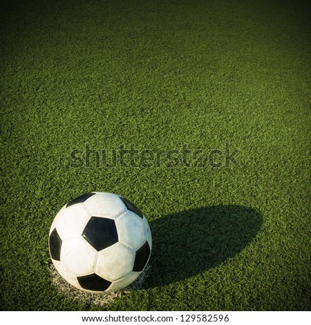 Soccer ball on green glass background