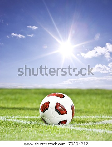 Soccer ball on green grass and blue sky background - stock photo