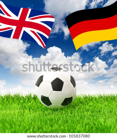 soccer ball on green grass and national german and british flag over dramatic blue sky