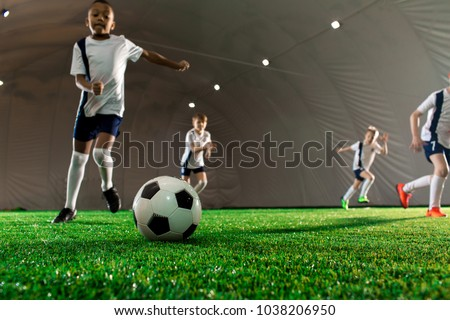 Soccer ball on green pitch and little players running towards it during game #1038206950