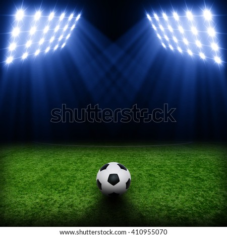 Soccer ball on green stadium, arena in night illuminated bright spotlights #410955070