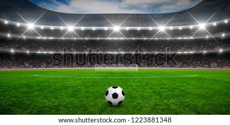 Soccer ball on stadium, arena in night illuminated spotlights