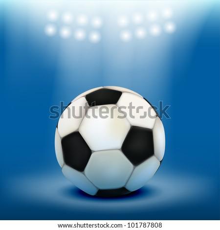 Soccer ball on stadium field grass, illuminated by floodlights