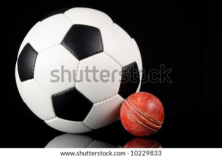 Soccer ball or football and a cricket ball.  Two games with worldwide followings that began in the United Kingdom or England. Reflection in black table top