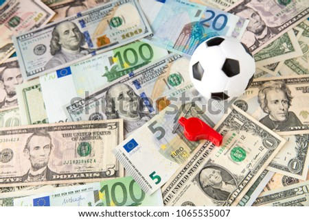 soccer ball over a lot of money. corruption football game. Betting and gambling concept. wold cup 2018. European cup . UEFA Champions League. premier league. bundesliga. la liga. calcio serie a. #1065535007