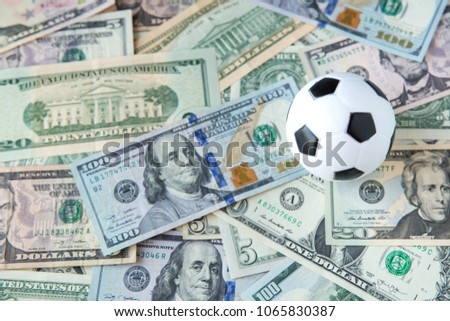 soccer ball over a lot of money. corruption football game. Betting and gambling concept. wold cup 2018. European cup . UEFA Champions League. premier league. bundesliga. la liga. calcio serie a. #1065830387