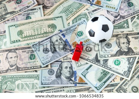 soccer ball over a lot of money. corruption football game. Betting and gambling concept. wold cup 2018. European cup . UEFA Champions League. premier league. bundesliga. la liga. calcio serie a. #1066534835